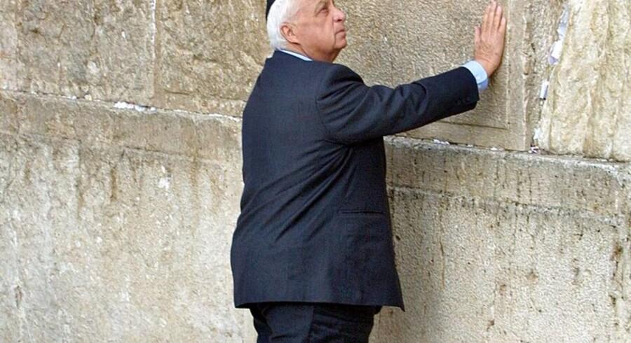 Ariel Sharon lægger sin hånd på GrædEmuren i det gamle Jerusalem. Datoen er 7. februar 2001 - dagen efter hans jordskredssejr over rivalen Ehud Barak, som havde lavet samme gestur 21 måneder tidligere, da han vandt over Benjamin Netanyahu.