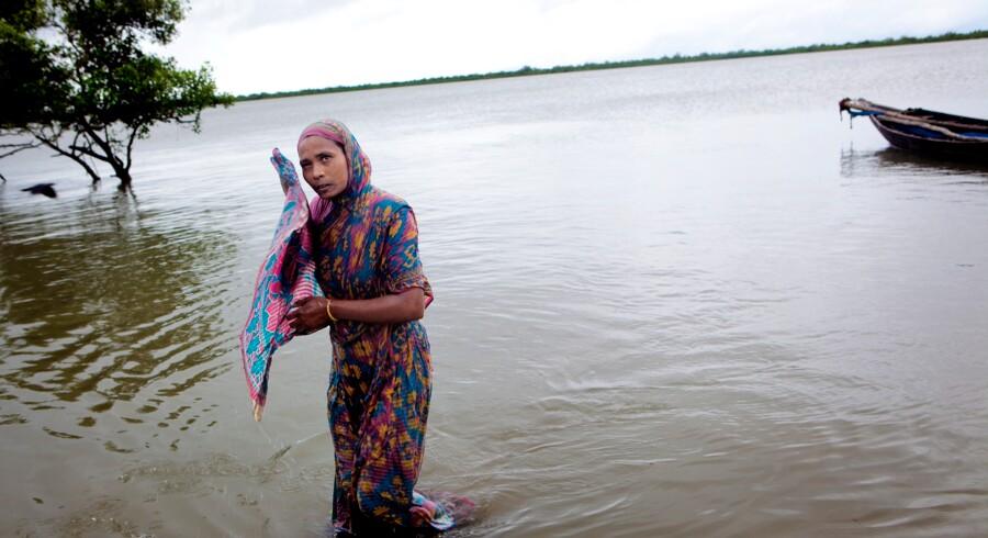 Jharna Begum har taget et bad i floden beskidte vand. Lige som resten af byens kvinder bader hun fuldt påklædt mens det står på. At bade i floden er den eneste mulighed hun har for at blive nogenlunde ren.