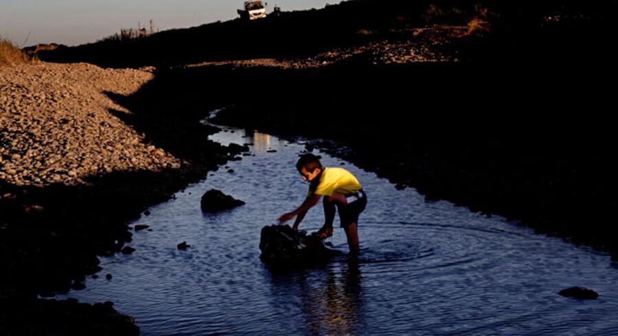 Der er ikke meget sjov i at gå ned til floden længere for børnene, der bor langs med den. Michel vader ud i Khabour få meter før det sted, hvor den før så store flod simpelthen løber tør. En død flod. Det nordøstlige Syrien har været tørkeramt de seneste tre og et halvt år. Sidste gang familien Mouchi så en dråbe regn var i januar. Det har efterladt jorden knastør, afgrøderne skrigende på vand og menneskene lidende i heden. I lange perioder er Khabour floden simpelthen helt tør. En død flod. Det er der flere grunde til. En er at vandet bliver brugt af en stadig voksende befolkning og en dertil hørende stadigt mere tørstig landsbrugssektor. Men det er ikke til at komme udenom at vejret også har ændret sig, at klimaet er forandret. Det har i mange år regnet mindre end normalt og i juli udsendte FN for tredje år i træk en international tørkevarsel for det nordøstlige Syrien og det nordvestlige Irak.