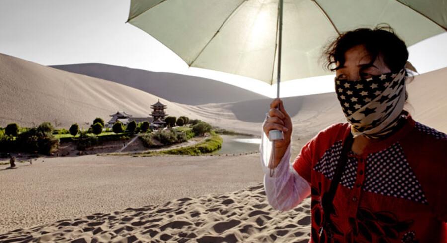 Ørkenspredning truer Kina. Tal fra FN's konvention om bekæmpelse af ørkendannelse viser, at ørkenen hver år spreder sig gennemsnitligt ind over 2.460 km2 land. Det svarer til et areal på lidt under Fyns størrelse, og næsten 400 millioner kinesere lever i de berørte områder. Ørkenspredning skyldes typisk klimaforandringer og menneskelige aktiviteter. På billedet ses en kvinde, der skærmer sig for den barske sol i ørkenen i det nordvestlige Kina.