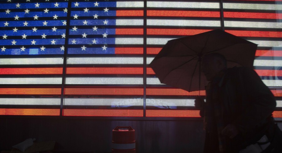 A man walks past a lit US flag with an umbrella at Times Square as it rains in New York, November 26, 2013. A powerful storm dumped heavy rain and snow over much of the eastern United States on Tuesday, threatening to snarl travel plans for millions of people over the busy Thanksgiving holiday, forecasters said. REUTERS/Carlo Allegri (UNITED STATES - Tags: SOCIETY ENVIRONMENT)