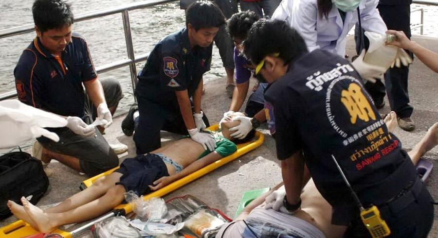 Redningsmandskab giver førstehjælp til passagerer fra færgen, der sank ud for Pattaya i Thailand.