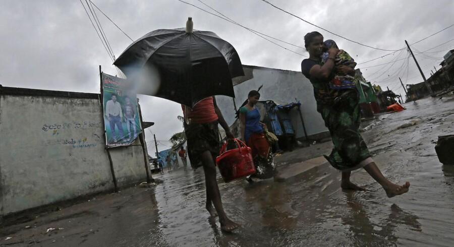En mor fører sit barn og sig selv i sikkerhed i landsbyen Donkuru i Andhra Pradesh-området i Sydindien. Lørdag aften gik cyklonen Phailin i land længere nordpå.
