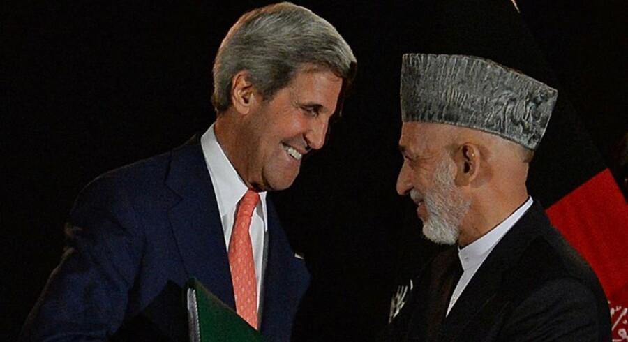 Den amerikanske udenrigsminister John Kerry og Afghanistans præsident, Hamid Karzai, giver hånd efter et pressemøde i Kabul 12. oktober 2013.