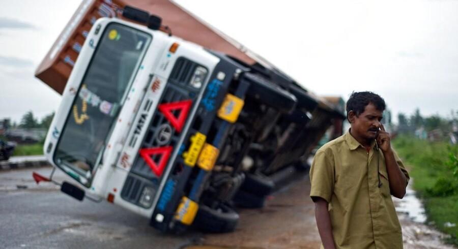Antallet af dræbte blev holdt nede - men de materielle skader er ikke til at overse. Her taler lastbilchauføør Jairam Yadav i telefon efter at hans køretøj er blevet væltet af kraftig sidevind på hovedvejen mellem Andhra Pradesh og Orissa.