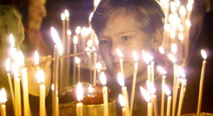 Søndag i Rusland var sorgens og eftertænksomhedens dag efter afslutningen lørdag på det blodige gidseldrama. Her tænder en dreng lys for ofrene ved en mindehøjtidelighed i Moskva. Foto: Reuters, Scanpix