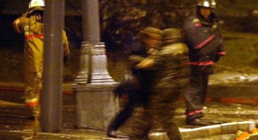 Et kvindeligt gidsel hjælpes af en officer fra specialstyrkerne, der indtog teatret. Foto: EPA