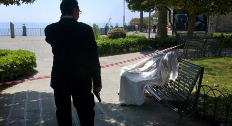 Aci Castello udenfor Catania: En betjent holder vagt ved et uidentificeret lig, der er fundet liggende på en bænk, efter en skudveksling den 1. august. Foto: AP/Scanpix