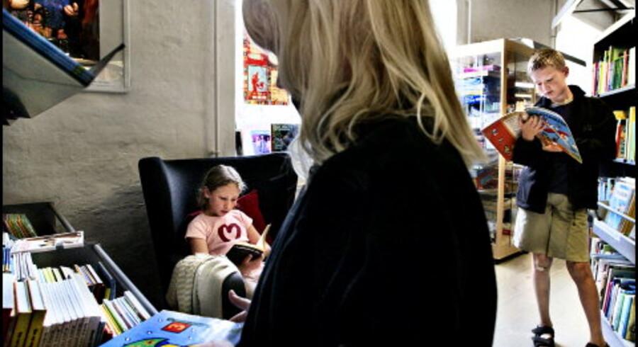 Lamija Begovit hygger sig i læsestolen på Københavns Kommunes bibliotek på Jemtelandsgade på Amager, hvor hun kommer næsten hver dag. Også Simone og Thomas Dahl fra Nordjylland er på jagt efter en god bog til ferien hos sin far i København. <br>Foto: Rune Feldt-Rasmussen <br>