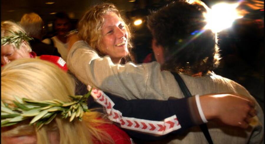 Katrine Fruelund fik et varmt knus af sin mor, da guldpigerne og håndfuld af de øvrige danske OL-deltagere i går vendte hjem fra Athen til Københavns Lufthavn. Fans og familie gjorde modtagelsen til »et sindssygt cirkus,« som landsholdsspiller Rikke Hørlykke udtrykte det. Foto: Morten Juhl<br> <br>