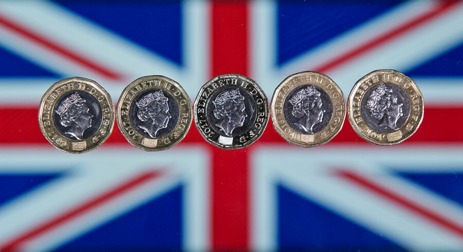 British one pound sterling coins are arranged in front of a Union flag for a photograph in London on December 14, 2017.  Justin TALLIS / AFP