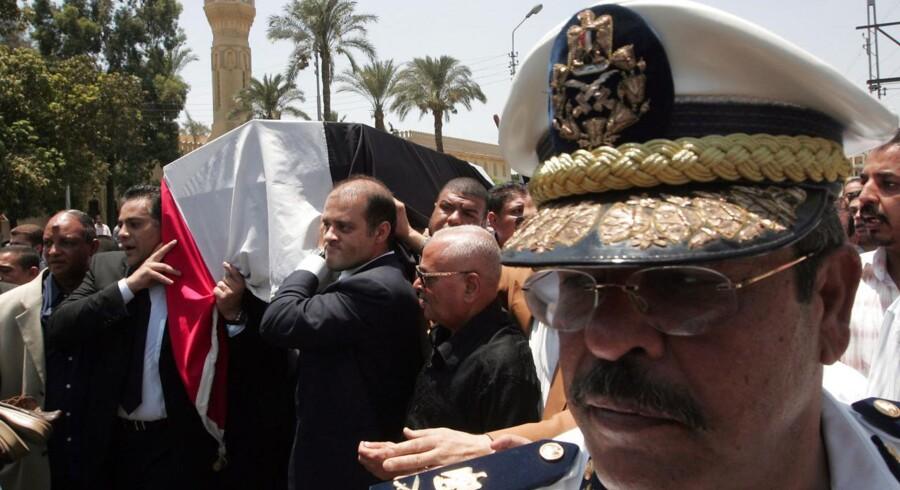 Gamal (t.v.) og Ahmed Marwan bærer deres fars kiste i Cairo i 2007. Faren, den egyptiske milliardær Ashraf Marwan, døde efter et fald fra en altan i London, kort efter at det blev afsløret, at han sandsynligvis havde spioneret for Israel.