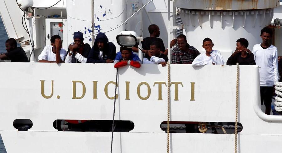 I sidste uge samlede det italienske kystvagskib »Diciotti« 190 migranter op fra overfyldte både i Middelhavet på deres vej fra Libyen mod Europa. Men 150 af dem er stadig ikke kommet i land. De sidder i stedet i en havn på Sicilien og venter på, at Italien og EU finder ud af, hvem der skal tage imod dem.