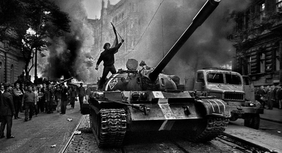 En Prag-borger står på toppen af en sovjetisk tank under invasionen af Tjekkoslovakiet i 1968.