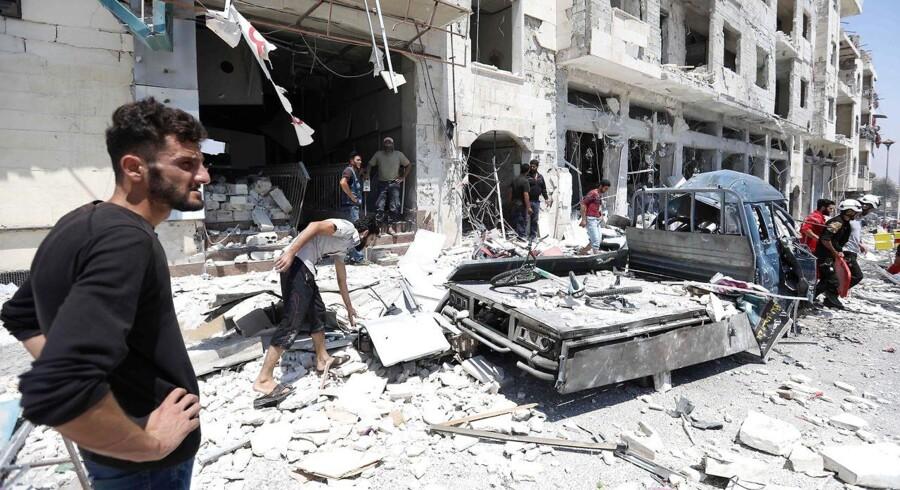 Syrere samler sig, efter en bilbombe tidligere i august sprang i luften i byen Idlib.
