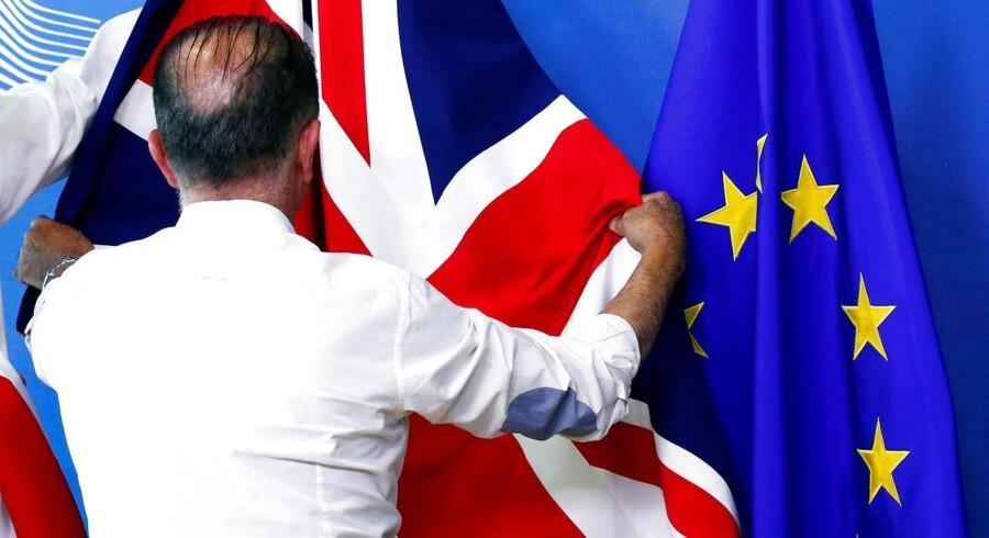 Det britiske flag, Union Jack, foldes ud ved siden af et EU-flag, inden et møde mellem Storbritanniens nye Brexitminister, Dominic Raab, og EUs chefforhandler, Michel Barnier 19. juli.