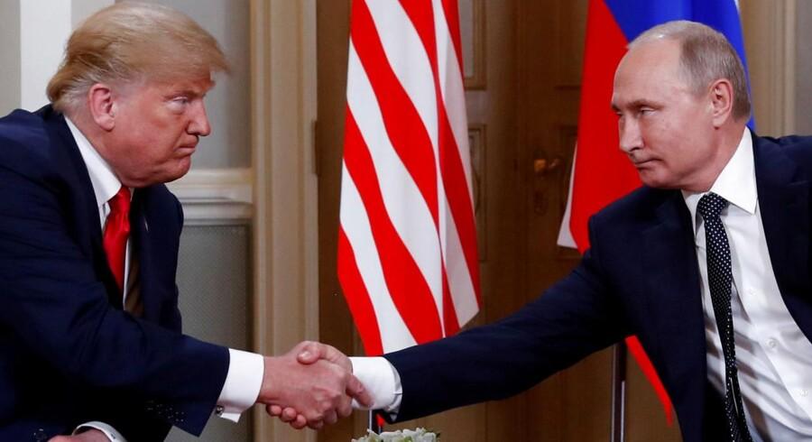 Donald Trump og Vladimir Putin trykker hinanden på næven under topmødet i Helsinki. Foto: Kevin Lamarque/Reuters/Ritzau Scanpix
