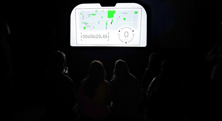 Arkivfoto: Tilskuere betragter en videopræsentation fra en Uber-begivenhed i New York City. En ny amerikansk bog går i dybden med distortion som fænomen - og hvordan virksomheder kan lide kraftigt, hvis deres forretningsmodel er for endimensionel. Uber blev stiftet i 2009 og har siden haft omfattende konsekvenser for taxi-industrien på tværs af byer, lande og kontinenter.