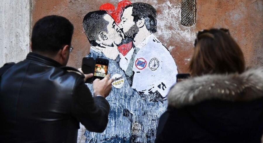 Luigi Di Maio og Matteo Salvini, der leder henholdsvis Movimento 5 Stelle og Lega, har været omhyggelige med ikke at lade sig fotografere sammen under de seneste dages intense regeringsforhandlinger. Imens har karikaturtegnere og andre satirikere travlt med at skildre dem i nærkontakt - som her på et vægmaleri i det centrale Rom.
