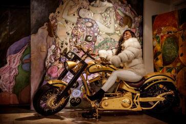 »Slotsfruens« motorcykel er parkeret foran et vægmaleri af hendes fem døtre, inspireret af maleren Gustav Klimt. Yvonne Seier Christensen har ikke kun en passion for biler, hun er også glad for motorcykler, her på sin Lauge Jensen-motorcykel.