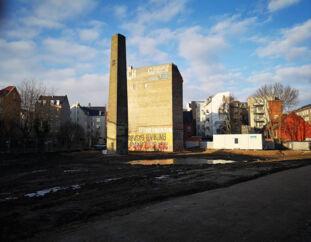 Skorstenen ved de gamle slagtergårde på Vesterbro, efter at den blev gjort 11 meter kortere på grund af nedstyrtningsfare. Nu vil borgmesteren have bygherren til at genopføre den i sin oprindelige højde.