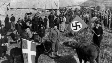 Det rygtedes hurtigt blandt lokalbefolkningen at de fremmede flag på fabrikken kunne beskytte dem mod japanerne. Her står Sindberg med hagekorsflaget, som tilhørte hans tyske kollega Karl Günther (midt i billedet). Det er Sindbergs kinesiske tolk Li Yulin, der står med Dannebrog.