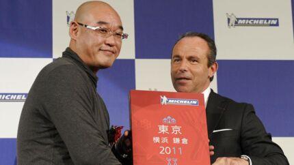 Michelin Guides direktør Jean-Luc Naret (th.) overrækker Mitsuhiro Araki (tv.) en forstørret udgave af 2011s Michelin Guide, hvor Araki første gang fik tilddelt tre michelinstjerner. Nu har de ingen.