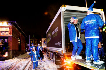 En af lastbilerne med julebryg og nissemænd og -kvinder i julemandskostume og nissehuer.