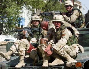 Amerikanske soldater redder en såret kollega fra en politistation i Bagdad efter et angreb 25. maj 2004. Efter amerikanernes likvidering af den iranske general Qassem Soleimani i fredags, opfordrede det irakiske parlament søndag den irakiske regering om at sende de amerikanske styrker ud af Irak.