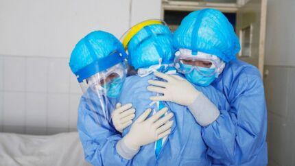 Tre sundhedsmedarbejdere iført sikkerhedsdragter krammer hinanden på en isolationsstue i et hospital i byen den kinesiske by Zouping.