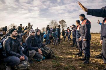 En gruppe syriske flygtninge har sat sig for at vise, at de ikke ønsker konfrontation. De vil blot hen til grænseporten til Grækenland. Det tyrkiske politi stopper dem. Få øjeblikke senere får de alligevel lov til at fortsætte helt ind til den lukkede grænse.
