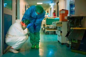 En sygeplejerske har beskyttende maske på og forsøger at trøste en anden, da de skifter vagt 13. marts 2020 på sygehuset i Milano.