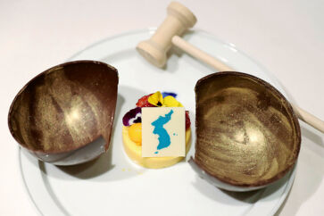 """This undated picture released by the South Korean presidential Blue House on April 24, 2018 shows a mango mousse cake decorated with a garnish in the shape of a unified Korean peninsula, which will be served at the dinner of the upcoming inter-Korean summit. The cake is in a wooden bowl, a symbol of Cold War confrontation, which will be broken by a hammer to symbolize the start of reconciliation. Symbolism will be the main course of a banquet at the upcoming inter-Korean summit, Seoul revealed on April 24, with a menu featuring Pyongyang's signature dish and food from the home towns of the South's leaders at previous meetings. / AFP PHOTO / The Blue House AND AFP PHOTO / handout / RESTRICTED TO EDITORIAL USE - MANDATORY CREDIT """"AFP PHOTO / THE BLUE HOUSE"""" - NO MARKETING NO ADVERTISING CAMPAIGNS - DISTRIBUTED AS A SERVICE TO CLIENTS"""
