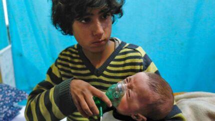 En dreng holder en iltmaske over et spædbarns ansigt i Douma i Østghouta ved den syriske hovedstad Damaskus efter et kemisk angreb den 22. januar. Samme område blev udsat for endnu et kemisk angreb den 1. februar. / AFP PHOTO / HASAN MOHAMED