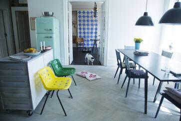 I køkken-alrummet står, hvad Vibeke Rohland kalder 'fællesbordet', hvor der bliver holdt middage, møder og i det hele taget lavet alt muligt. Bordpladen ligger løst på bukkene, hvilket er funktionelt og nemt at rokere rundt med – lige som de to skuffemoduler i køkkenet er flytbare. Spisebordsstolene har parret købt på Lauritz.com. De er designet af Folke Pålsson i 60erne, og Vibeke Rohland har betrukket ryggene med eget tekstil. Plaststolene i gul og grøn er designet af Robin Day og passer fint ind i hjemmets fleksible indretning, fordi de kan stables. Vibeke Rohlands tekstil i baggrunden skjuler døren ind til datteren Sedsels værelse.